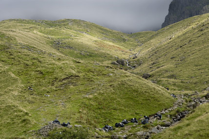 A long shot of bags of stone used for path restoration on Scafell, the highest summit in England, at Wasdale, Cumbria