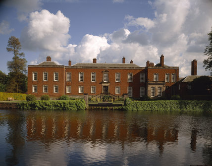 North front of Dunham Massey with moat in foreground.