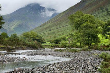 Great Gable, with its summit wreathed in cloud, looms over the river at Wasdale, Cumbria