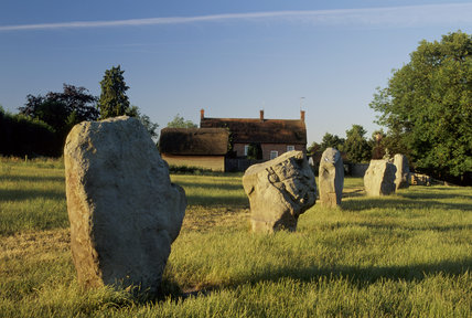 Some of the stones at Avebury with one of the cottages beyond