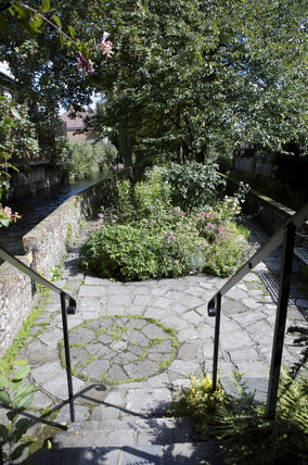 Iron steps down into the garden alongside the River Itchen at C18th Winchester City Mill, Hampshire