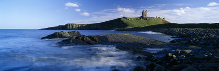 The ruins of Dunstanburgh Castle standing out against the sky, seen from the boulder strewn Embleton Bay