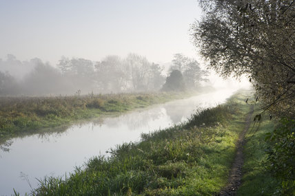 Hazy light on the towpath alongside the River Wey Navigations near Guildford, Surrey