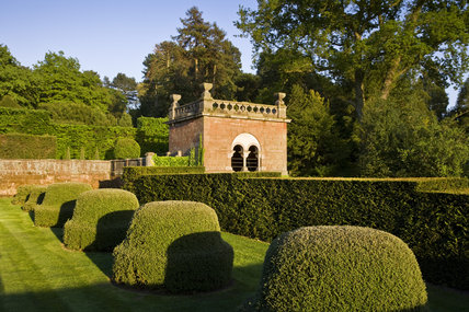 View over topiary mounds towards the Shelter House at the end of the Dahlia Walk at Biddulph Grange Garden, Staffordshire