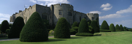 The exterior of Chirk Castle, flanked by clipped yew trees