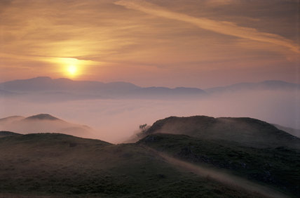 Cumbria, Eskdale Dawn from Blea Tarn Hill near Boot white mist rising over green hills