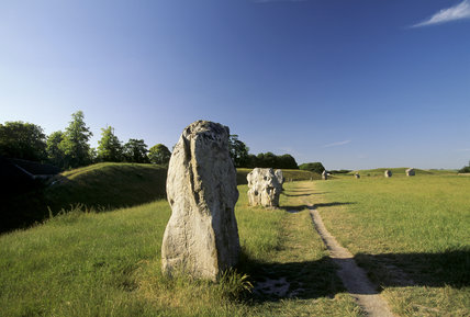 A row of standing stones set in a grassy landscape at Avebury which is one of the largest henge monuments and stone circles in the British Isles, dating from 3000-2000 B.C.