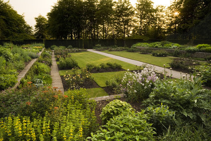 Sunset over the Rose Garden at Castle Drogo, near Exeter, Devon, with a series of square and rectangular beds set into a lawn