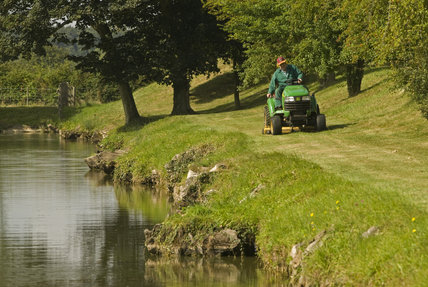 Mowing the grass on the terraces of the restored Elizabethan garden at Lyveden New Bield, Peterborough, Northamptonshire