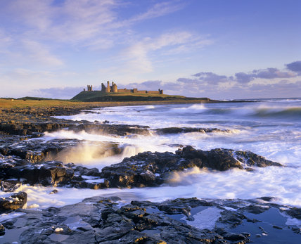 Waves breaking on the long beach at Craster looking towards Dunstanburgh Castle, Northumberland