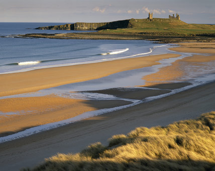 Dunstanburgh Castle viewed from the north west, shot from high dunes behind Embleton Beach