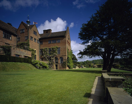 The exterior of Chartwell, former home of Sir Winston Churchill, seen from the garden with a deep blue sky, and a tree to the right