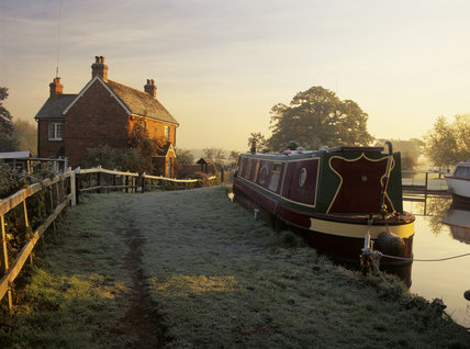 Lock-keepers' cottage with narrowboat moored in the foreground on a frosty autumnal dawn at Papercourt Lock, River Wey Navigation