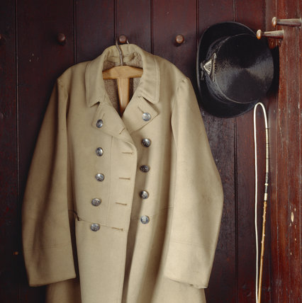 Detail of a coat, hat and whip on display in the Tack Room at Charlecote Park
