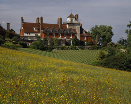South front of Standen with neat striped lawn leading down to field of yellow buttercups