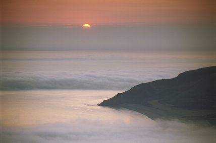 The sun rising out of the mist on Bossington Hill