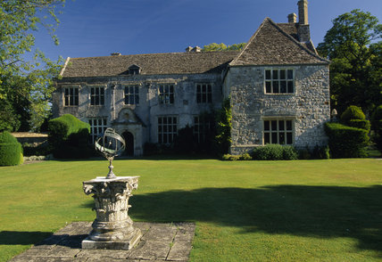 The front of the Manor catching the oblique sunlight, with an armillary sphere on a plinth in the foreground