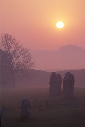 Avebury Stone Circle at Sunrise, a misty landscape with rising sun