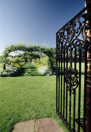 Open wrought iron gate at Beningbrough Hall leading to a colourful garden with a pergola