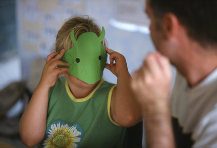 Close-up of a little girl trying on her insect mask made out of green paper, during the `Bug Safari' activity funday at Wicken Fen