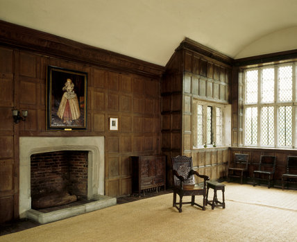Room view of the Great Parlour showing the fireplace, floor matting, bay window, four Cromwellian chairs, c. 1650