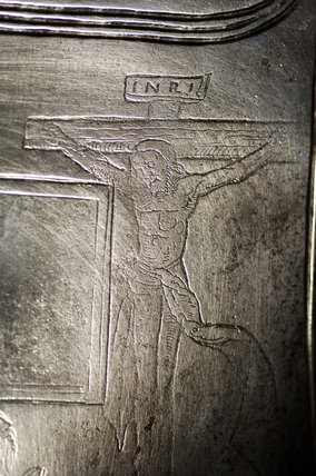 Close view of a German breastplate of 1540 engraved with a crucifix and kneeling knight, in Dragon at Snowshill Manor
