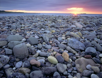 A view of a pebble beach towards the sea, the pebbles are a variety of colours and the horizon is a bright red orange glow