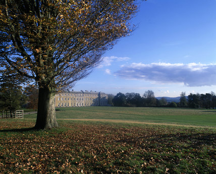 A distant view of the west front of Petworth House, seen across the grass