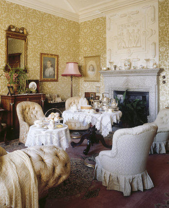 The Boudoir, attached to Lady Robartes's bedroom, furnished as a feminine sitting-room with tub chairs and gilt-framed watercolours