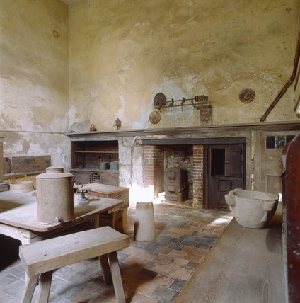 View of the Kitchen at Calke Abbey shown as it was found by the National Trust, with characteristic 19th century yellow lime- washing