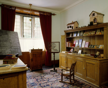 Room view of the School Room including the governess's desk, abacus, map, dresser with books and toys at Lanhydrock
