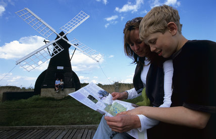 Young visitors outdoors near the windpump (windmill) at Wicken Fen, Cambridgeshire