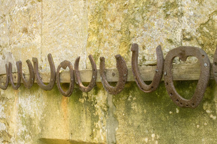A row of horseshoes mounted on the wall at Snowshill Manor, Gloucestershire, UK