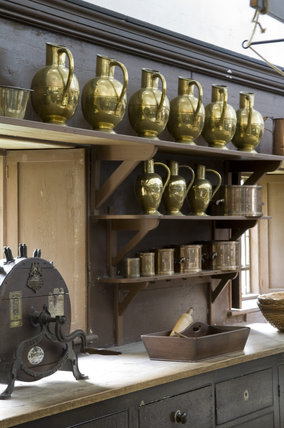 The Old Kitchen at Belton House, Lincolnshire, UK, showing an early nineteenth century compilation of shelves and utensils and a knife grinder