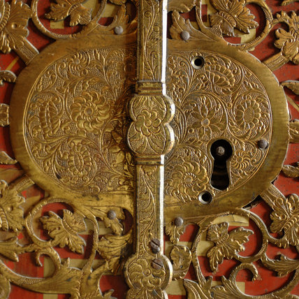 Close view of the lock detail of a French, red lacquered cabinet in the Grey Room at Snowshill Manor