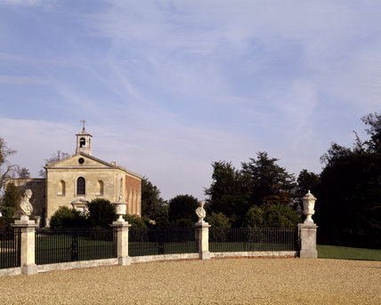 The forecourt and Church at Wimpole Hall with mounted busts and urns in the railings