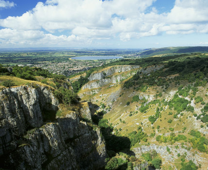 View of sunlit Cheddar Cliffs and Cheddar Gorge (the Gorge is not National Trust property) towards a distant skyline