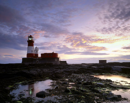 A view of Longstone Lighthouse across a rocky area with pools of water