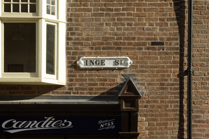 Exterior view of the Birmingham Back to Backs, showing the street sign for Inge Street and part of the signage for Candies, the sweet shop