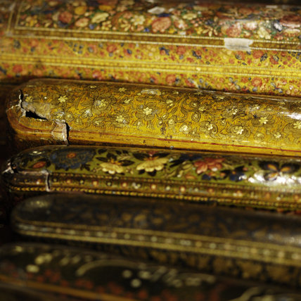 A collection of carved Persian lacquered pen and games boxes, part of the Charles Wade collection in Seraphim at Snowshill Manor, Gloucestershire