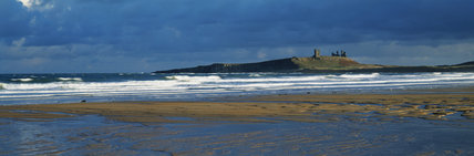 View across Embleton bay to Dunstanburgh castle with stormy sky