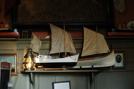 Model boats and a lamp on a shelf in Admiral at Snowshill Manor, a room of c.1720 with a collection of mainly nautical objects.
