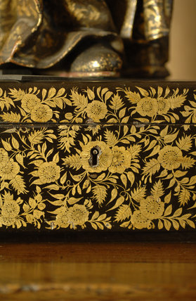 Close view of the gold flower and foliage decoration in Chinese style on a black and gold lacquer box in Nadir at Snowshill Manor, home of collector Charles Wade