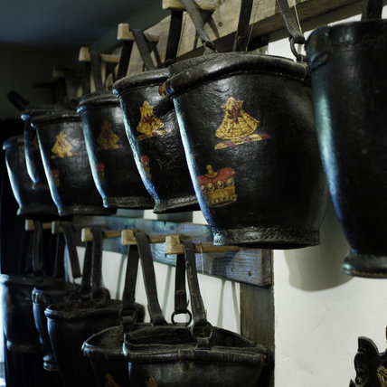Leather fire buckets in the Old Stairwell at Snowshill Manor, Gloucestershire