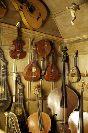 A mixed selection of stringed instruments including guitar, harplute and double bass, part of the musical instrument collection of Charles Paget Wade in the Music Room at Snowshill Manor, Gloucestershire