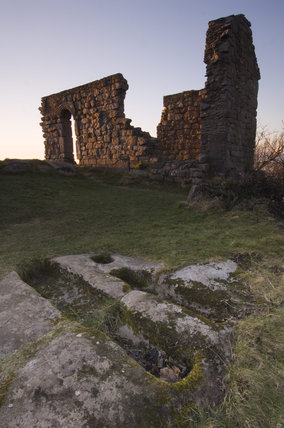 The ruins of St Patricks Chapel, Heysham Head, Lancashire, with rock-cut graves in the foreground