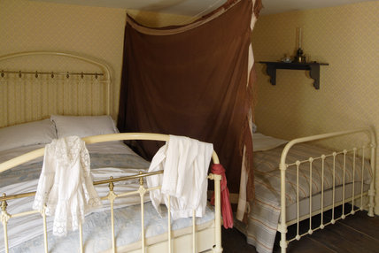 The second floor bedroom of the 1870s house at the Birmingham Back to Backs, with a curtain divider and two iron bedsteads
