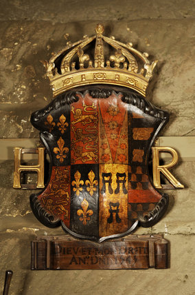 Coloured shield of the royal coat of arms of Henry VIII on the wall of Dragon, at Snowshill Manor