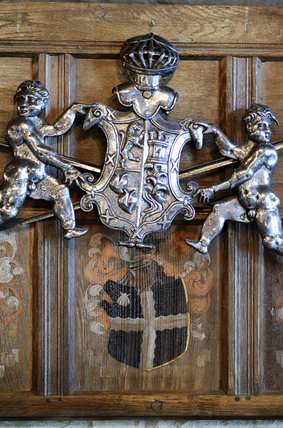 Carved coat-of-arms hang above a painted coat-of-arms on the wooden panellling, part of the Chales Wade collection at Snowshill Manor, Gloucestershire