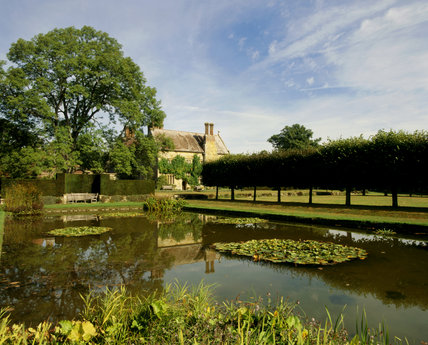 The garden at Bateman's with the pool in the foreground and the  C17th house, home to Rudyard Kipling, in the background